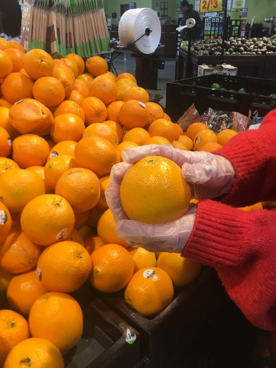 """A volunteer for """"Shopping Angels"""" holds an orange earlier this week."""