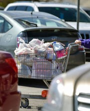 A shopping cart full of goods is pushed through a parking lot.