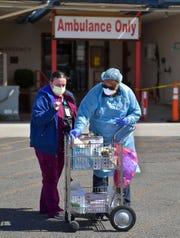 Tena Thomas, left, a medical assistant, and Media Mutanduki, a nurse practitioner, check supplies in their cart for Coronavirus screening outside the Barnett Clinic.