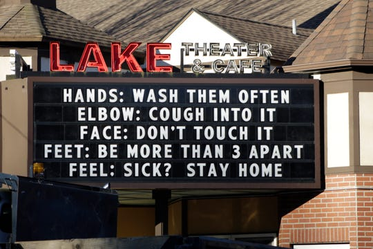 In this March 17, 2020 file photo, a marquee outside the Lake Theater & Cafe in downtown Lake Oswego, Ore., reminds people to practice social distancing and stay home if sick.
