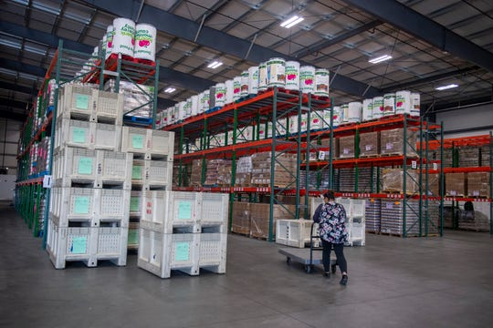 A Food Bank for Monterey County member pushes a cart inside the food bank warehouse on Thursday, March 19, 2020.