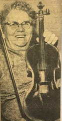 "Mrs. Laura Barrett smiles about her lovely ""Strad"" conversation piece during an interview in San Angelo in July 1959. Her husband bought the instrument in Menard in 1903, and according to the label, it is a copy of a Stradivarius."