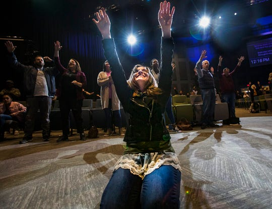 In this Sunday, March 15, 2020 photo, Heather Davis prays at the altar at the end of a service at Redemption to the Nations church in Chattanooga, Tenn. While most churches around Hamilton County decided to cancel services because of concerns over the COVID-19 coronavirus, Redemption to the Nations stayed open.