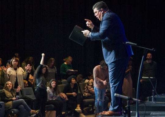 In this Sunday, March 15, 2020 photo, Redemption to the Nations church Lead Pastor Kevin Wallace preaches to his congregation about trusting God to help them get through the COVID-19 coronavirus threat in Chattanooga, Tenn. While most churches around Hamilton County decided to cancel services because of concerns over the disease, Redemption to the Nations stayed open.