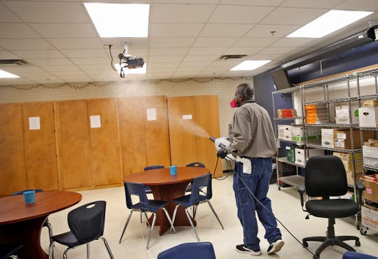 Ira Routt sprays disinfectant in a classroom at Central High School on Wednesday, March 18, 2020 as part of a district wide effort to prevent coronavirus.