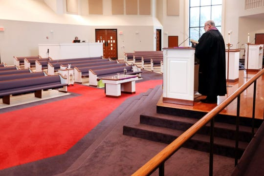 In this Sunday, March 15, 2020, photo, Rev. Kip Rush delivers his sermon in a sanctuary filled with mostly empty pews during a service at Brenthaven Cumberland Presbyterian Church in Brentwood, Tenn. The church decided to broadcast the service instead of holding a service with the entire congregation because of the COVID-19 coronavirus.