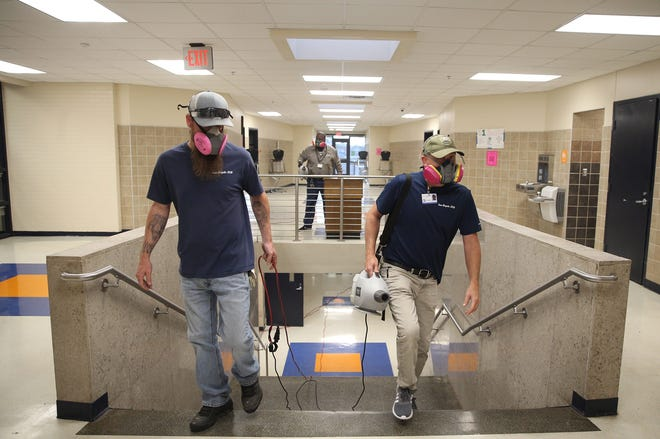 Cory Oliver, left, and Scott Goodwin, right, spray disinfectant at Central High School on Wednesday, March 18, 2020 as part of a district wide effort to prevent coronavirus.