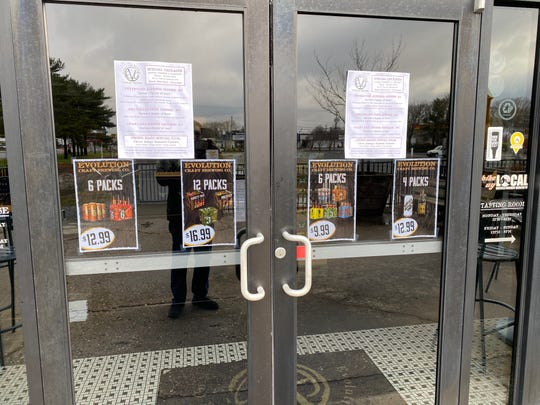 Signs on the front door at Evolution Craft Brewery in Salisbury indicate food and beer carryout options for customers.
