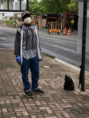 """Michael Mitchell waits for a bus at Market and Texas after finishing some banking business. He's wearing a mask because """"it's serious out here,'' he said."""