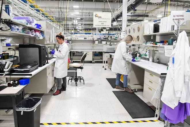Lab workers run tests in quality control on Thursday, March 19, 2020 at SAB Biotherapeutics in Sioux Falls.