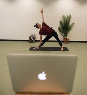 Brittni Whittington, the owner of Rising Om Yoga, demonstrates how she plans on providing yoga classes virtually to customers. Whittington set up her laptop on a wooden stool at her Bannerman studio to stream her class.