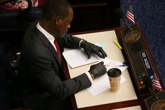 Rep. Al Jacquet wears rubber gloves while going over documents at this desk during the last day of the 2020 legislative session at the Capitol Thursday, March 19, 2020.