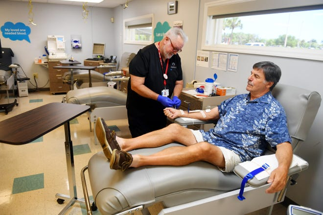 """Phil Gebow, of Vero Beach, prepares to donate blood on Thursday, March 19, 2020, at OneBlood Donor Center in Vero Bech. """"I come in about four times a year,"""" Gebow said. """"You're doing some good and helping people in need."""" Due to the coronavirus outbreak, hospitals are in need of blood donations. """"We've seen an uptick in donations over the last week which is always nice to see,"""" said Larry Thompson (left), team leader at the center."""