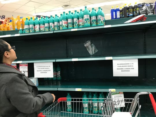 A shopper looks for bleach on near-empty shelves at a Juarez Smart supermarket on Wednesday, March 18, 2020.