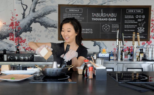 Yina Zarowitz, owner of Tabu Shabu in Thousand Oaks, makes an order of porridge to go in March. She later closed the restaurant before reopening it for takeout as the coronavirus crisis continued. Limited dine-in service at Tabu Shabu started on June 4.