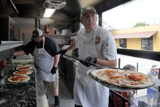 Phil Adler, right, owner of Freda's Pizza & Woodfired Kitchen, slides a pizza into the oven aboard the business' food truck in a photo taken on March 19. Adler has since discontinued food-truck operations to focus on takeout and possible delivery from his commercial kitchen in Westlake Village.