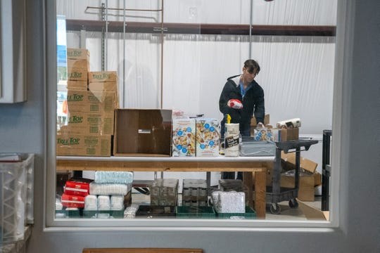 Volunteers work to distribute boxes of food to clients at the Visalia Emergency Aid Council food pantry on Thursday, March 19, 2020.