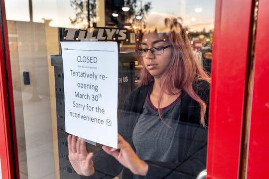 Annalise Allala posts a sign on locked doors at Tilly's on Wednesday, March 18, 2020. Tulare Outlets is closed until further notice due to COVID-19.