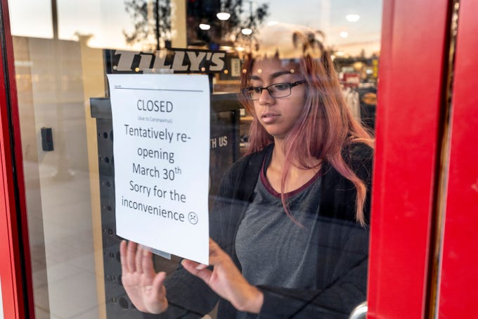 Annalise Allala posts a sign on locked doors at Tilly's on Wednesday, March 18, 2020. Tulare Outlets is closed until March 30 according to memo circulated among the stores.