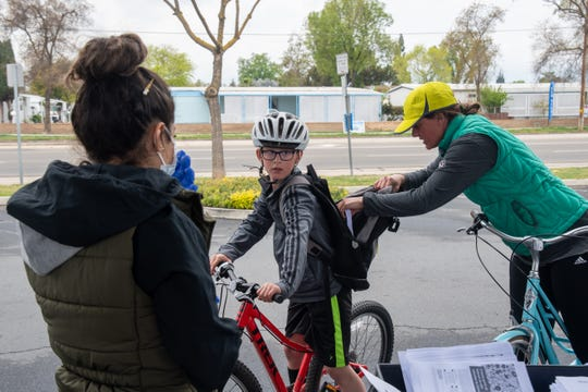 A parent puts an enrichment packet into a backpack at Willow Glen Elementary School on Thursday, March 19, 2020. Packets for grades TK-12 were available at each of the grab-n-go meal service sites. They have materials for 15 days, the equivalent of three school weeks.