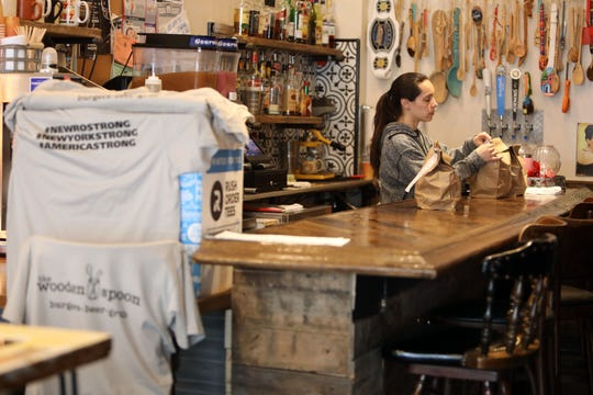 Maria Bongiorni packs delivery and pick-up orders at the Wooden Spoon in New Rochelle, NY March 19, 2020. #newrostrong t-shirts are being sold for $40 and with each shirt purchased, the buyer receives a $15 gift card and a meal will be donated to the first responders of New Rochelle.