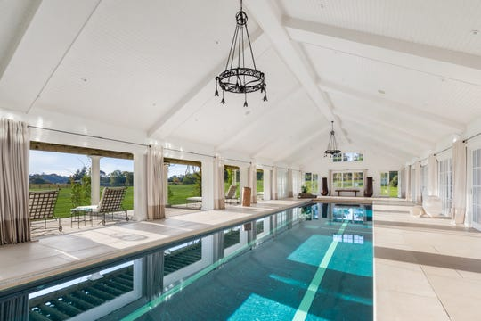 A 4,000-square-foot pavilion holds a 60-foot indoor pool, a grand stone fireplace with a lounge area, and French doors that fold open in warm weather. The pavilion also has a gym, spa, sauna and kitchen.