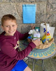 """Shayne Dalgleish, 10, from Rye Brook, a student at Iona Prep, show off his """"""""Sani Stash"""" at his home for the mail carriers, FedEx drivers, and other delivery persons, so they can disinfest themselves during their stop. """"Every little bit of caring helps our fellow Americans"""", his mom Yvonne Gasperino says. Photo supplied by the family, March 19, 2020."""