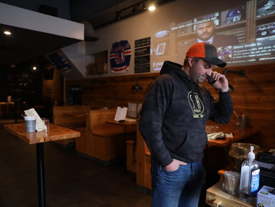 Justin Zeytoonian, co-owner of Smokehouse bar takes an order from a customer in Mamaroneck March 19, 2020. Multiple local bars and restaurants were looking forward to big-volume days with the NCAA Tournament almost then the NCAA cancelled the tournament admits coronavirus concerns.