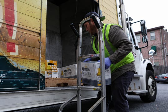 Joe Hoffmaster stacks cases of beer returned from Rockford Tavern into a distribution truck. He's been on the job only three weeks and has started wearing gloves during loading, he said, because he doesn't want to catch coronavirus and spread it to his grandfather.