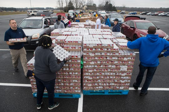 Thousands of people wait in line and pick up free food during an emergency drive-thru food pantry Thursday morning at Crossroads Community Church in Georgetown. The event was held by the Food Bank of Delaware. A third drive thru-pantry event will be held at 11 a.m. Friday, March 20, 2020 at Dover International Speedway. A picture ID and proof of Delaware residency is required to receive food.