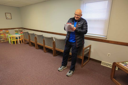 Henry Stoklosa, a patient at Dr. William Funk's primary care practice in Newark, fills out paperwork before seeing a nurse for a routine visit on Thursday morning. The office is taking extra precautions with treating his patients during the coronavirus outbreak by not allowing patient to sit in the waiting room to help reduce interaction and spreading of germs.