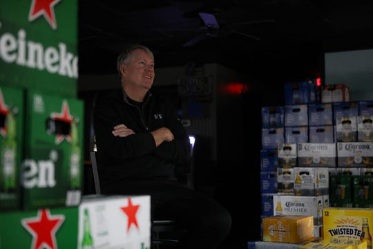 Paul Ogden, owner of multiple bars, poses among cases of beer that he's scheduled to return to the distributer on Thursday. His six bars only sell alcohol and are all closed due to the coronavirus outbreak.