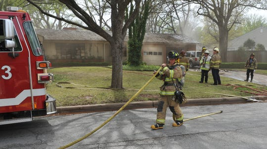 Wichita Falls firefighters work to contain a house fire at a home located in the 2400 block of Ellingham Drive, Thursday afternoon.