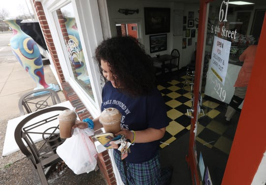 Julia Rouse picks up her take-out order at Ditty's Downtown Deli. Bar and restaurant owners are counting on the community's support to stay open following Gov. Mike DeWine's order to close dine-in eating. The restriction was put in place on March 15, to help slow the spread of the coronavirus.