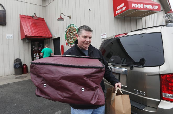 Owner Jim Watson carries delivery orders to his vehicle outside The Barn in Zanesville. With social distancing in effect to help stop the spread of the coronavirus, restaurants across Muskingum County are looking to delivery and take-out orders to stay afloat.