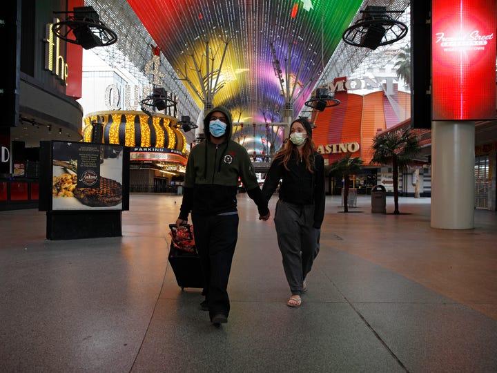 A couple wearing masks walks along deserted Fremont Street in Las Vegas on Wednesday night.