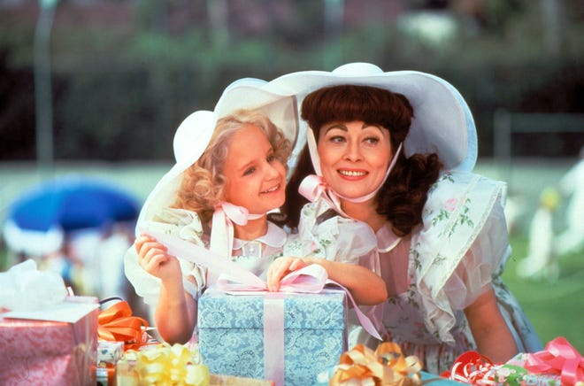 """It's all smiles for Christina (Mara Hobel, left) and Joan Crawford (Faye Dunaway) until the wire hangers come out in """"Mommie Dearest."""""""