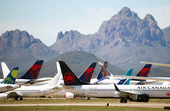 Three Delta Air Lines passenger jets are parked among other airliners at the Pinal Airpark on Tuesday, March 17, 2020 in Marana, Ariz. Due to the coronavirus outbreak, Delta wide-body aircraft are being moved to storage in Arizona.