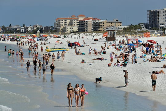 Visitors enjoy Clearwater Beach, Wednesday, March 18, 2020, in Clearwater Beach, Fla. Beachgoers are keeping a safe distance from each other to help protect from the spread of the new coronavirus.