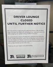 A sign at the Johnson's Corner truck stop says the driver lounge is closed because of the coronavirus outbreak. Drivers can usually relax and watch TV on lounge chairs at the stop during mandatory rest periods.