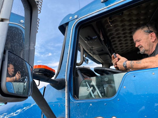 Trucker Ron Applegate, 57, looks at his phone while talking to his wife while parked at the Johnson's Corner truck stop between Denver and Cheyenne.