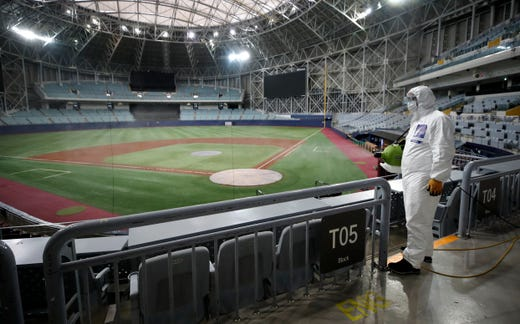 A worker wearing protective gears disinfects as a precaution against the new coronavirus at Gocheok Sky Dome in Seoul, South Korea, Tuesday, March 17, 2020. The Korea Baseball Organization has postponed the start of new season to prevent the spread of the new coronavirus. For most people, the new coronavirus causes only mild or moderate symptoms. For some it can cause more severe illness.