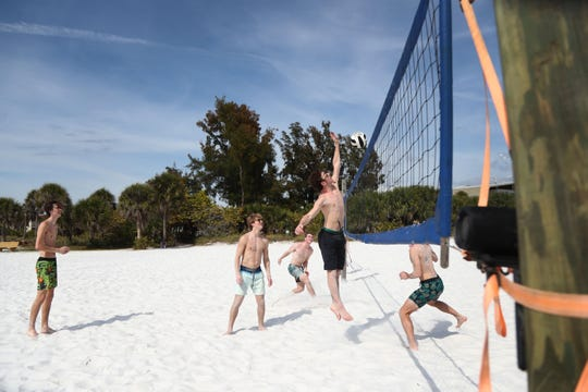 Students on spring break from Iowa play volleyball at Siesta Key Beach.