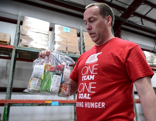 Donal Dickens, Upstate SC Branch Manager of Second Harvest Food Bank of Metrolina holds a United Way of Anderson County weekend snack pack of food in Anderson Friday, March 20, 2020.