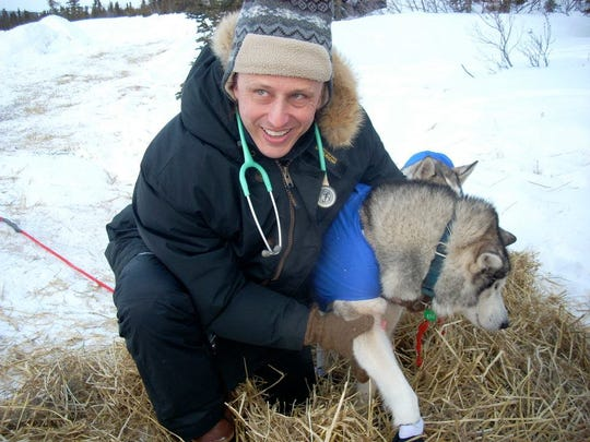 Veterinarian Glenn Behan, a Manchester resident, inspecting a dog at the Inditarod Dog Sled Race in Alaska.