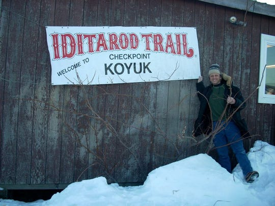 Veterinarian Glenn Behan of Manchester poses next to a sign at one of the checkpoints during the Iditarod Dog Sled Race.