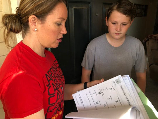 Abilene Independent School District special education teacher Amy Petrencik, left, reviews printed assignments with her Clack Middle student Caiden Becker on Thursday. Caiden, 13, is stuck at home while schools across the country are closed due to the coronavirus outbreak.