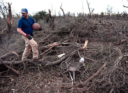 Cody Carson carries a basketball he found amid the toppled trees on his property on FM 126 south of Merkel on Thursday.