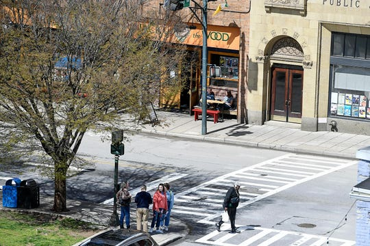 Despite the closure of restaurants and schools amid coronavirus concerns, people walked and shopped in downtown Asheville March 17, 2020.