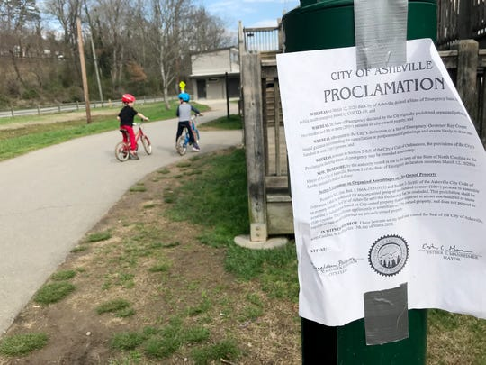 """A proclamation posted at Carrier Park and dated March 12 stated """"it shall be prohibited for any organized group of one-hundred or more persons to assemble"""" amid the city's state of emergency caused by COVID-19. Despite coronavirus concerns, parks along the French Broad River were crowded with people March 19, 2020 in Asheville."""